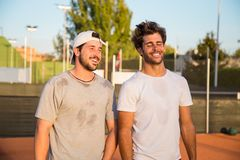 Laughing tennis players. Two tennis players standing on tennis court during break and laughing Stock Images