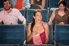 Laughing In A Theater. Laughing women with popcorn in a theater Stock Photography