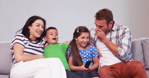 Laughing then afraid family watching tv stock video