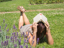 Laughing thin woman. A woman laughing his head with a book Stock Image