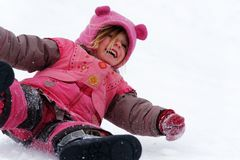 A laughing child sliding in the snow royalty free stock photography