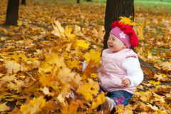 Laughing toddler and falling leaves Royalty Free Stock Images