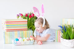 Laughing toddler girl in blue dress and bunny ears. Happy laughing toddler girl with curly hair wearing a blue dress and bunny ears playing with Easter presents Royalty Free Stock Photos