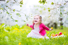 Laughing toddler girl eating apple in blooming garden Royalty Free Stock Photography