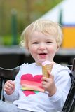 Laughing toddler girl eating ice-cream outdoors Stock Images