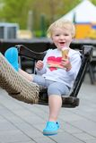 Laughing toddler girl eating ice-cream outdoors Royalty Free Stock Image