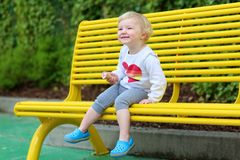 Laughing toddler girl eating ice-cream outdoors Stock Photo