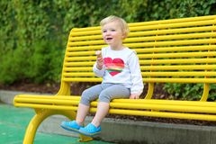 Laughing toddler girl eating ice-cream outdoors Royalty Free Stock Photography