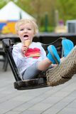 Laughing toddler girl eating ice-cream outdoors Royalty Free Stock Photos