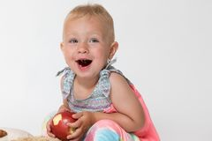 Laughing toddler girl is holding red apple Royalty Free Stock Images