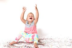 Laughing toddler girl is sitting on the floor. Fallen confetti a Stock Photos
