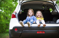 Laughing toddler girls sitting in the car Stock Photos
