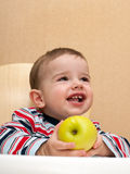 Laughing toddler holds an apple Royalty Free Stock Photos