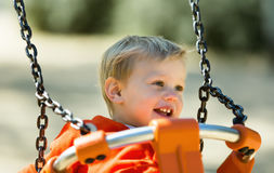 Laughing toddler on orange swing Royalty Free Stock Photo