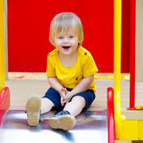 Laughing toddler on the slide. Happy and excited toddler on the playground slide Royalty Free Stock Photo