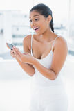 Laughing toned brunette holding mobile phone Stock Photos