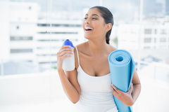 Laughing toned brunette holding sports bottle and exercise mat Stock Image