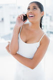 Laughing toned brunette phoning with mobile phone Royalty Free Stock Photography