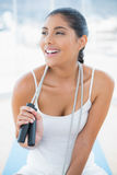 Laughing toned brunette sitting on floor with skipping rope Royalty Free Stock Photos