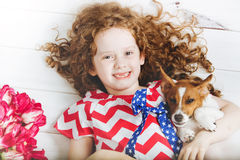 Laughing toothless girl hugging a puppy. Family celebration 4th july. Independence Day concept. Laughing toothless girl hugging a puppy Royalty Free Stock Photos