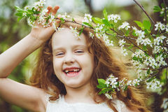 Laughing toothless girl in white dress near blooming cherry tree. S. Happy, healthy smile Stock Photos