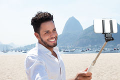Laughing tourist at Rio de Janeiro with selfie stick Stock Images