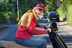 Laughing trendy senior woman with a zest for life. Riding along on her scooter wearing a peaked cap, scarf and sunglasses stock image