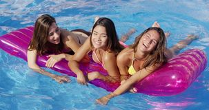 Laughing trio of young women in swimming pool. Laughing trio of young women floating on purple air cushion in outdoor swimming pool on bright sunny day stock video