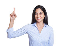 Laughing turkish businesswoman pointing up Stock Image