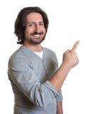 Laughing turkish guy pointing sideways Royalty Free Stock Image
