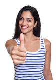 Laughing turkish woman in a striped shirt showing thumb up. Laughing turkish with long black hair in a striped shirt showing thumb up on an isolated white Stock Photo