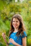 Laughing Tween Girl with Messy Hair Holding a Stick. A laughing tween girl with messy hair stands with a stick in hand, looking into the camera with a wrinkled Royalty Free Stock Photos