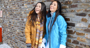 Laughing twins in jackets and glove near wall Stock Photo
