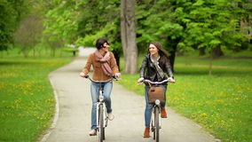 Laughing Two Female Friends are Riding on Bicycles in the Park. Young Funny Women with Bikes Spending Time Together. stock video footage