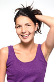 Laughing vivacious natural woman. With her hand to her tousled brown hair smiling joyfully at the camera, upper body portrait on white Royalty Free Stock Images