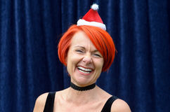 Laughing vivacious redhead in a Santa Hat Royalty Free Stock Photography