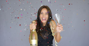 Laughing vivacious woman celebrating the New year. With falling confetti  streamers and a magnum of champagne  studio over grey Royalty Free Stock Photos