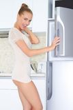 Laughing vivacious woman opening freezer Royalty Free Stock Photos