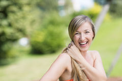 Laughing vivacious young woman outdoors. Laughing vivacious young woman with her long hair in a ponytail sitting outdoors in a park enjoying the summer sunshine Stock Photo