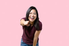 Laughing vivacious young woman pointing Stock Photos