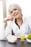 Laughing vivacious young woman. Sitting at the breakfast table enjoying a healthy meal Royalty Free Stock Photo