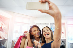 Laughing vivacious young women posing for a selfie. Together in a fashion store as they hold up their purchases in colorful bags Stock Images