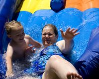 Laughing on Water Slide. Young boy and mother playing on water slide Royalty Free Stock Photography