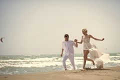 Laughing wedding couple on beach. Beautiful laughing young wedding couple of men and women in white running along ocean beach shore on windy weather sunny day stock photos