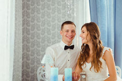 Laughing wedding couple sits at the dinner table. With blue candles Royalty Free Stock Image