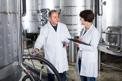 Laughing wine maker shows to expert equipment Royalty Free Stock Photo