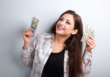 Laughing winner young woman holding dollars and happy looking up Royalty Free Stock Photography