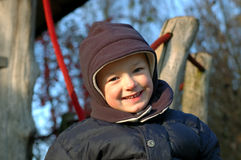 Laughing winter child. Boy child playing on playground in winter and laughing royalty free stock photography