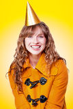 Laughing winter party girl on yellow background Stock Photography