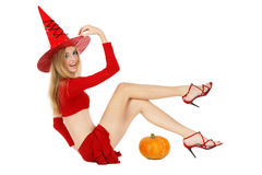Laughing witch. Beautiful blond girl with long legs in costume of Halloween witch lying on white background and smiling Stock Images